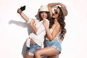 picture of selfie  - two young women taking selfie with mobile phone  - JPG