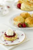 foto of devonshire  - English Cream tea scene with scones Cornish style on china plate with cake stand behind - JPG