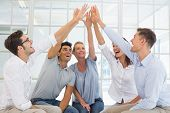 image of 5s  - Group therapy in session sitting in a circle high fiving in a bright room - JPG