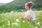 stock photo of daisy flower  - 7 years old child having fun in flower field - JPG