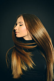 picture of hair motion  - Beautiful girl with magnificent long hair in motion posing over black background - JPG