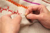 stock photo of thread-making  - Woman hands sewing with needle and thread