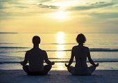 image of  practices  - Young couple practicing yoga in the lotus position on the ocean beach during sunset - JPG
