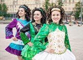 stock photo of wig  - Three women in irish dance dresses and wig posing outdoor  - JPG
