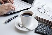 stock photo of peppy  - businessman running and a cup of coffee on him desktop - JPG