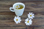 picture of chamomile  - chamomile and chamomile tea on a wooden table