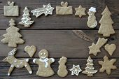 stock photo of ginger bread  - White Decorated Ginger Breads on Wood Building Frame Background with Copy Space - JPG
