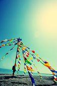 stock photo of tibetan  - Buddhist Tibetan prayer flags waving in the wind against blue sky - JPG