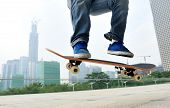 stock photo of skateboarding  - young  skateboarder legs skateboarding jumping at city - JPG