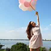 foto of legs air  - Fashion girl with  air balloons over blue sky - JPG