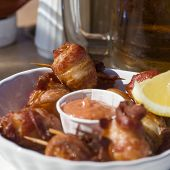 stock photo of scallops  - Deep fried bacon wrapped scallops with seafood sauce and lemon at an outdoor cafe - JPG