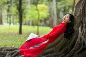 image of recliner  - Pretty slim young Vietnamese lady dressed in red traditional clothes relaxing on aerial tree roots in a public park reclining on her back as she stares thoughtfully into the air - JPG