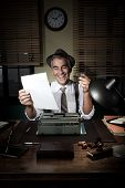 pic of 1950s  - Cheerful reporter at work having a drink 1950s style office.