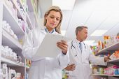 picture of prescription pad  - Young trainee writing on a prescription pad in the pharmacy - JPG