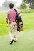 stock photo of golf bag  - Golfer walking away holding golf bag at golf course - JPG