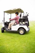 foto of buggy  - Golfer driving in his golf buggy in golf course - JPG