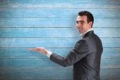 image of presenting  - Businessman presenting with hand against wooden planks - JPG