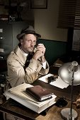 foto of trench coat  - Confident detective smoking at desk in trench coat 1950s film noir style - JPG