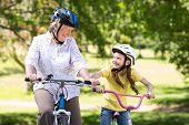image of granddaughters  - Happy grandmother with her granddaughter on their bike on a sunny day - JPG