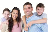 picture of piggyback ride  - Portrait of happy parents giving piggyback ride to children against white background - JPG