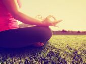 stock photo of instagram  -  hands of a woman meditating in a yoga pose on the grass toned with a retro vintage instagram filter app or action effect - JPG