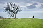 image of nightfall  - Woman sitting alone on a beach above the sea - JPG