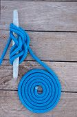 stock photo of dock  - Blue rope coiled on a wooden dock and tied to a metal dock cleat - JPG