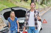 stock photo of nervous breakdown  - Couple after a car breakdown at the side of the road - JPG