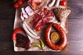stock photo of deli  - Assortment of deli meats on parchment on wooden table background - JPG