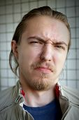 foto of character traits  - Portrait of a very evil and distaste young man with a beard and mustache - JPG