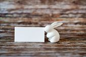 foto of white rabbit  - Close up Small Easter Rabbit Figurine with Empty White Rectangular Greeting Card on a Rustic Table - JPG