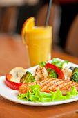 stock photo of salmon steak  - Tasty dish of salmon steak with vegetables and juice - JPG