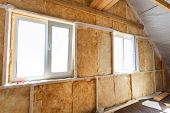 stock photo of glass-wool  - Inside wall heat isolation with mineral wool in wooden house building under construction - JPG