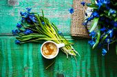 picture of vase flowers  - scilla siberica flowers in a vase and cup of coffee in rustic interior - JPG
