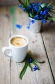 stock photo of vase flowers  - scilla siberica flowers in a vase and cup of coffee in rustic interior - JPG
