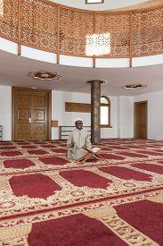 stock photo of islamic religious holy book  - Black African Muslim Man Reading Holy Islamic Book Koran - JPG