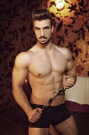 foto of handcuff  - Sexy macho man with handcuffs in hotel room on bed