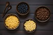 stock photo of dark side  - Crispy chocolate and simple corn flakes and honey flavored breakfast cereal in rustic bowls with fresh blueberries and wooden spoons on the side photographed overhead on dark wood with natural light - JPG