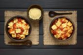 foto of dark side  - Baked ravioli with homemade tomato sauce in rustic bowls with grated cheese and wooden spoons on the side photographed overhead on dark wood with natural light - JPG