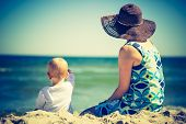 stock photo of mother baby nature  - Vintage photo of small child with mother on sea shore. Beautiful landscape with baby and mother photographed from behind