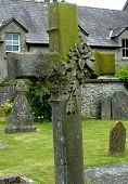 stock photo of irish moss  - moss covered cross with roses carved onto it in ireland - JPG