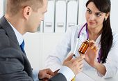 foto of antidepressant  - Beautiful female medicine doctor giving to male patient in business suit jar of pills - JPG