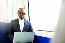 picture of commutator  - Young African American Businessman Using his Laptop Computer Seriously While Commuting on a Train - JPG