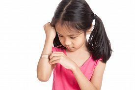 pic of hurt  - Little asian girl hurt with bandage on her arm isolated on white background - JPG