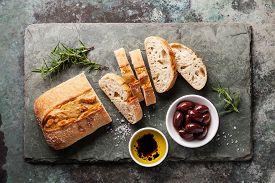 stock photo of slating  - Fresh ciabatta with olive oil and olives on stone slate background - JPG