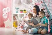 Happy loving family. Pretty young mother reading a book to her daughters indoors. Funny mom and love poster