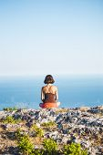 A Girl Is Sitting On Top Of A Mountain At Sunset. A Woman Is Engaged In Yoga And Sits In A Lotus Pos poster