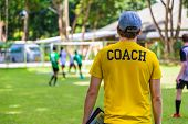 Back View Of Male Soccer Or Football Coach In Yellow Shirt With Word Coach Written On Back, Standing poster