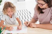 Little Kid Drawing A House Using Colorful Crayons With His Female, Therapist During A Meeting In The poster