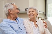 Romantic senior couple laughing while sitting on sofa. Elderly married couple smiling on sofa at hom poster